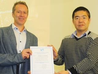 Branch Chair Dr. Yunnan Gao presents a Certificate of Appreciation to Gary Carswell of Aegion.